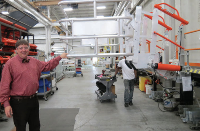 Figure 1 – Rob Honeycutt stands by a SafeRack loading gangway being put together on the assembly line. The structure, which can hold thousands of pounds, can be adjusted up and down with one hand.