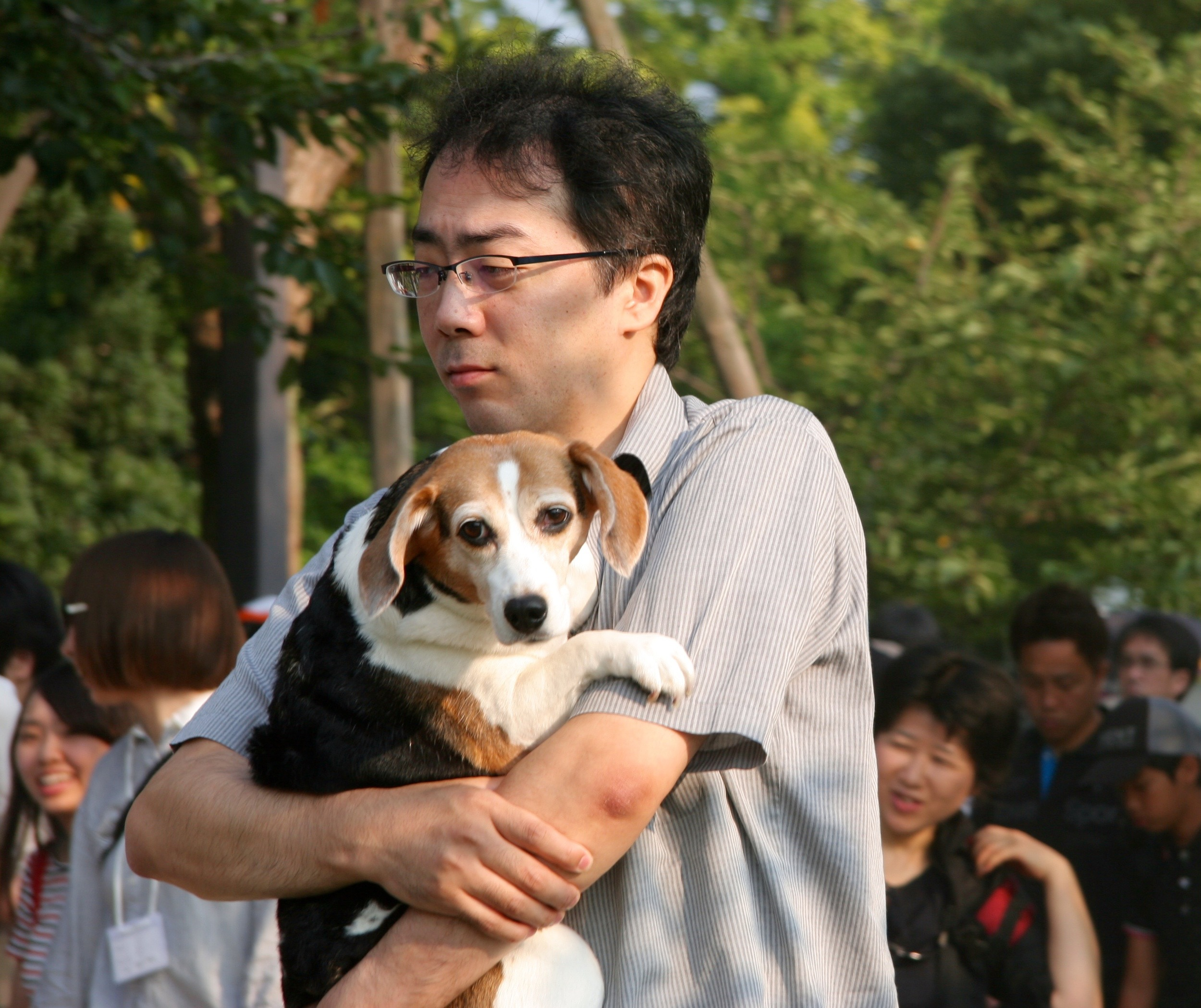 A man totes his obese beagle around the park grounds, the only dog I saw all day. True love