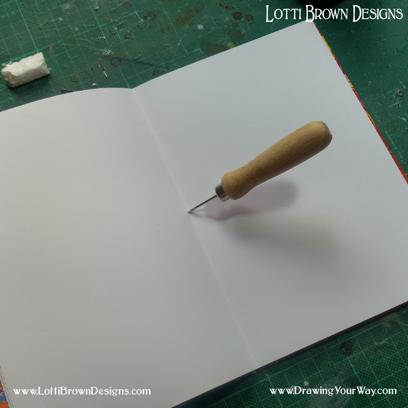 Using a bradawl to make a hole in the centre of the sketchbook