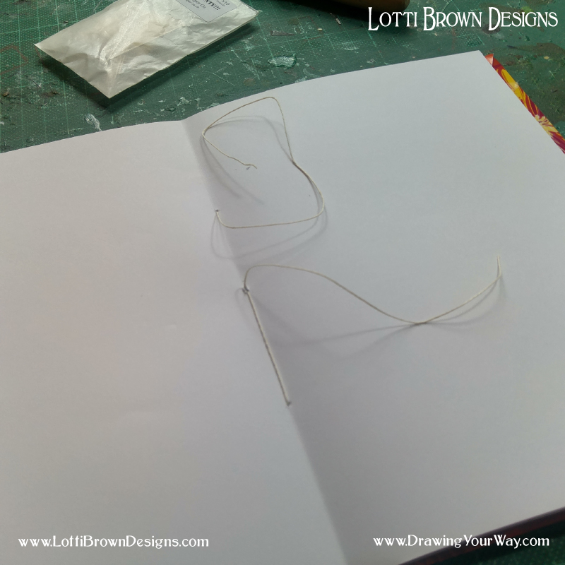 Pull the stitches tight so that the sketchbook holds together securely