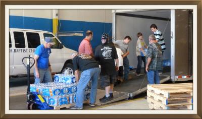 Bikers for Jesus help with unloaded cases of water.