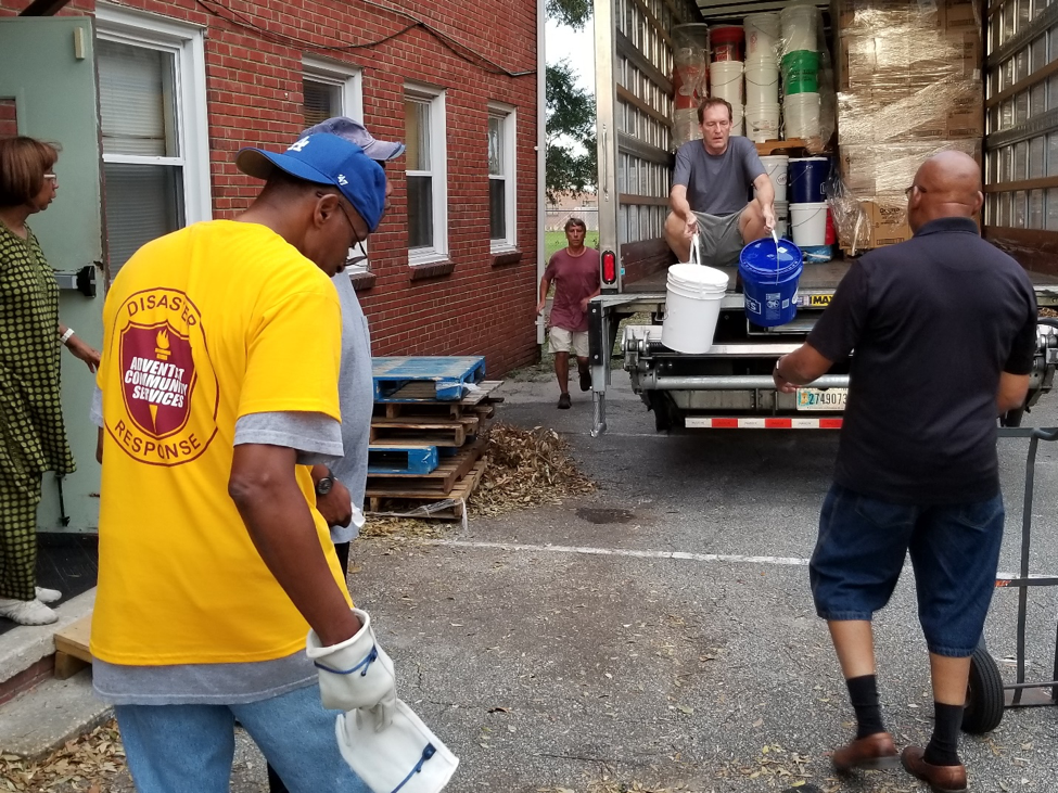 Volunteers unloading donated supplies from the truck to send to Distribution Centers.