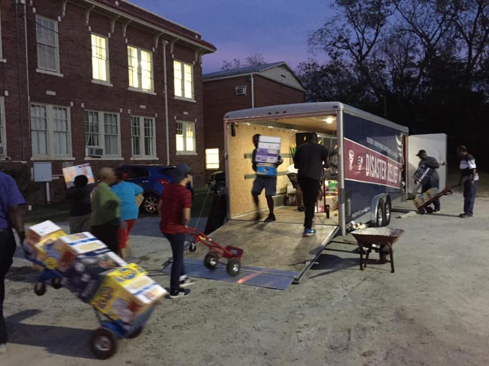 Volunteers from the Ephesus SDA Church in New Bern assist in unloading the trailer.