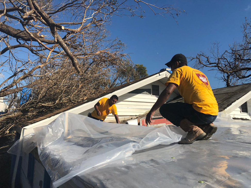 ACS DR workers place plastic on roof damaged by Hurricane Michael.
