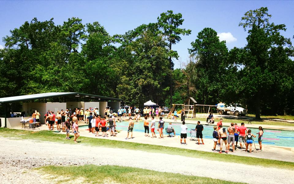 Athletes standing around waiting for their turn in the pool for the swim relay this weekend.