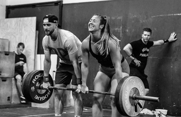Ryan and Rebecca doing partner deadlifts as Greg makes sure the wall doesn't move on them.