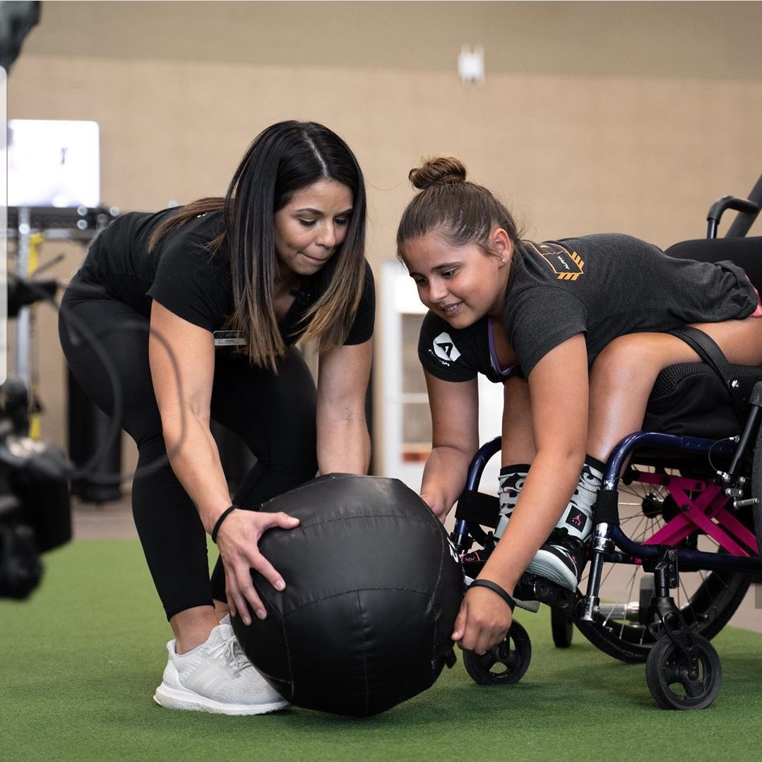 Here is one of our coaches Crystal Flores training an adaptive athlete. Six of our coaches successfully attended the  CrossFit Adaptive Athlete Training course.