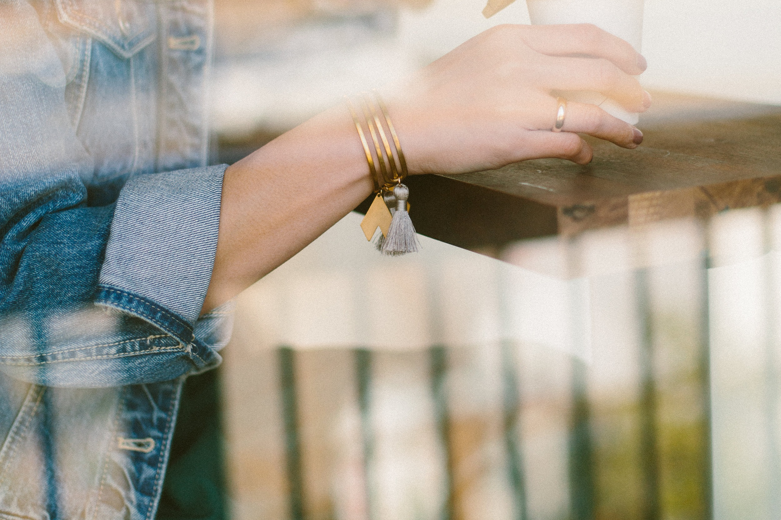 Close up of woman wearing cadia gold raw brass cutout cuff bracelet + gray nylon silk tassels, jean jacket, coffee, double exposure.jpg