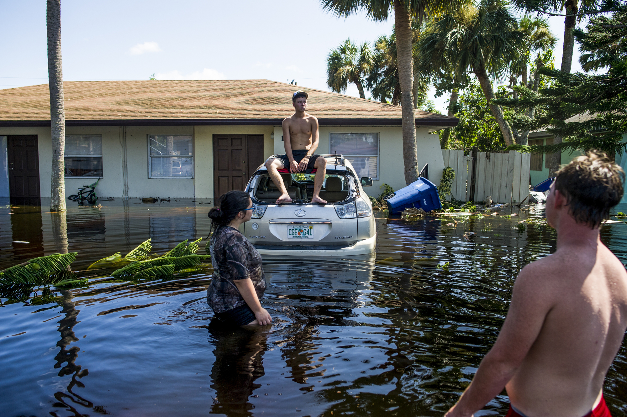 Hunter Londy sits atop Andy Vo's flooded car, windows broken from the winds,in Bonita Springs.