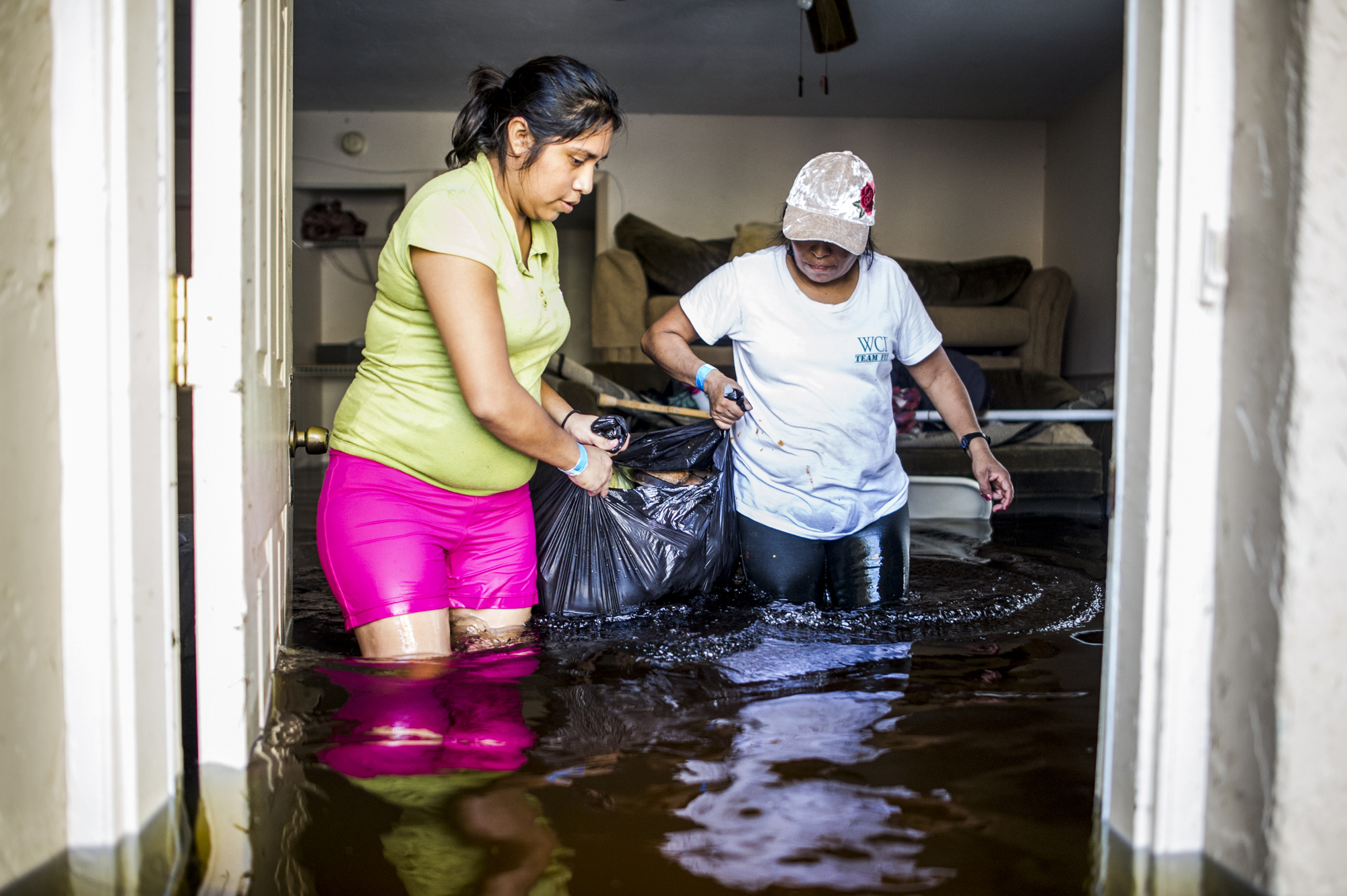 Nayeli Vasquez, left, and her aunt, Basilica Ventura, right, carry the last salvageable valuables out of their flooded home in Bonita Springs.