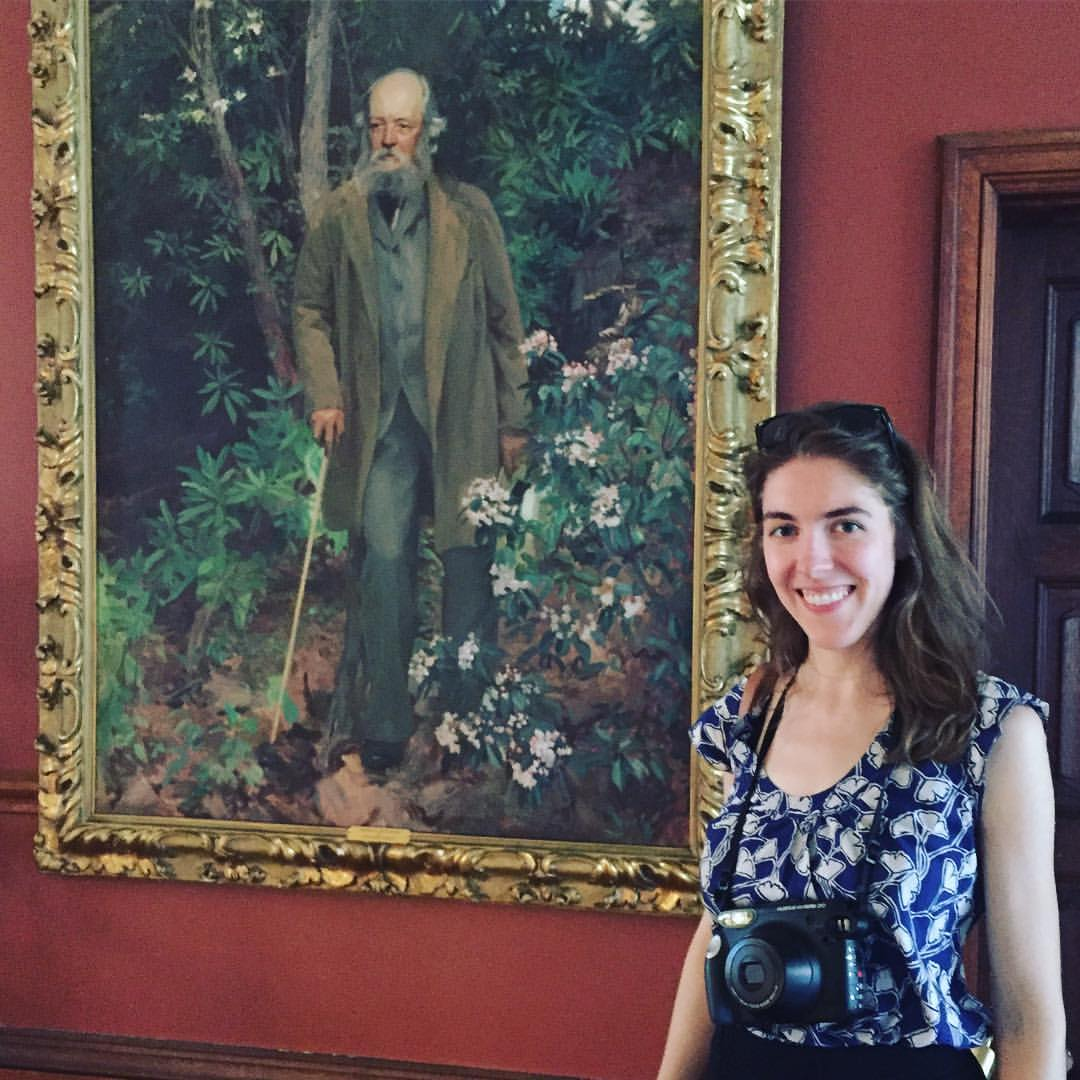 Ashley Yazdani stands next to a painting of Frederick Law Olmsted, one of the creators of Central Park.