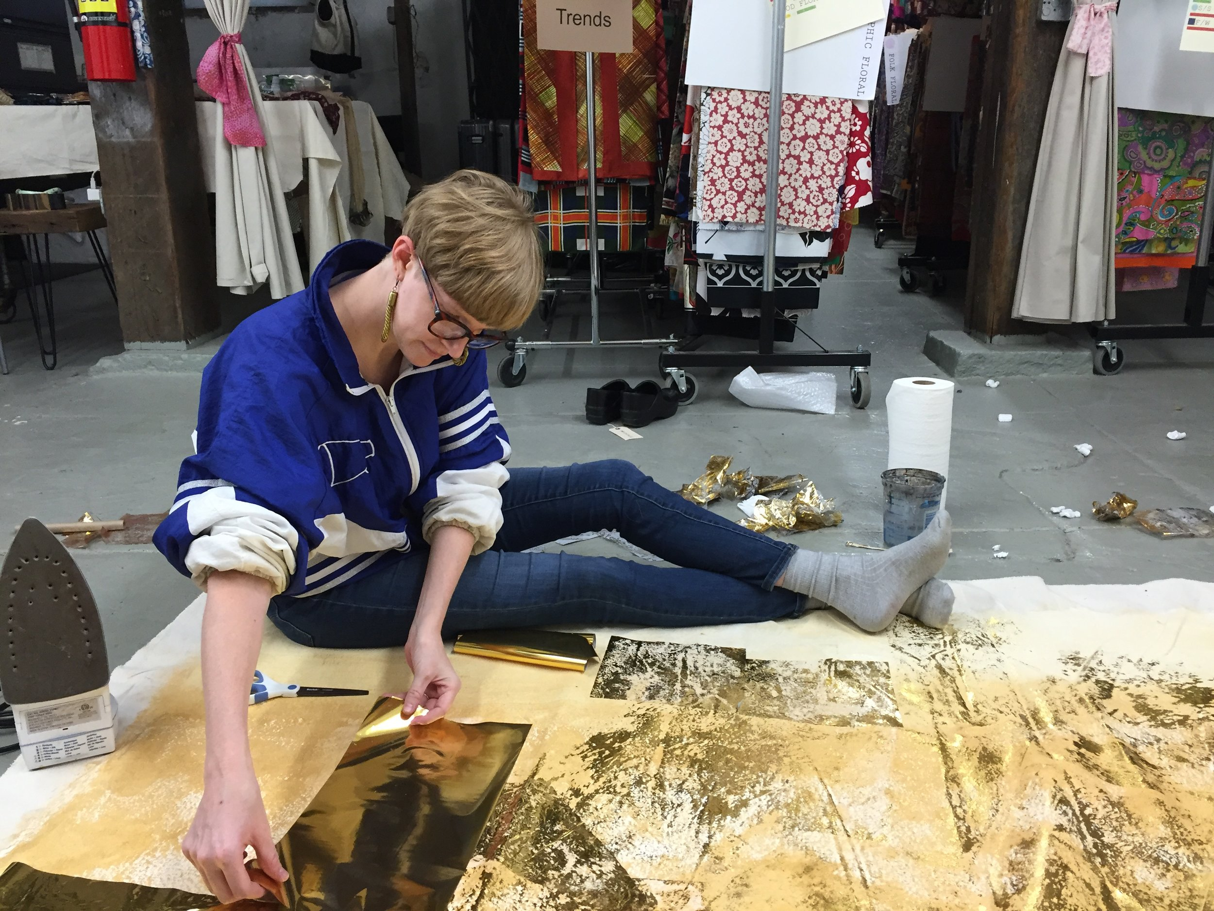 Emily Joynton applies gold foil to canvas, creating the backdrop that will hang in the PF Vintage booth at trade shows.