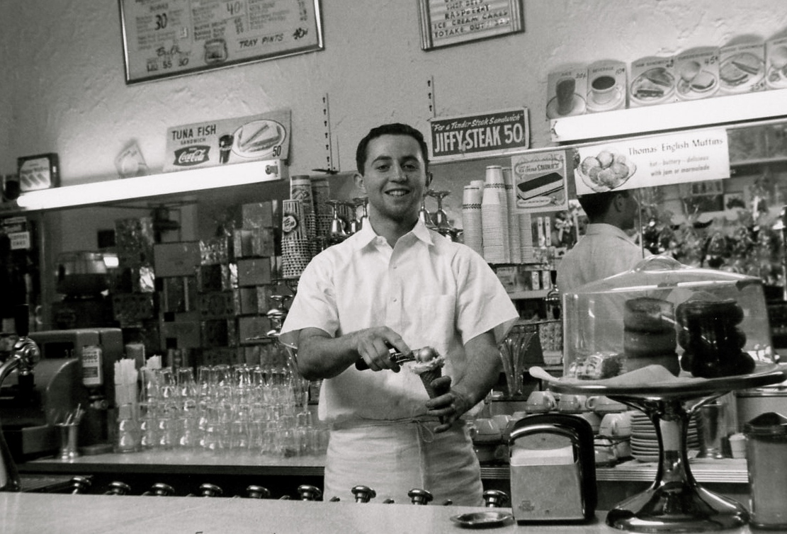 1958 Pete Panarites working behind the counter after School