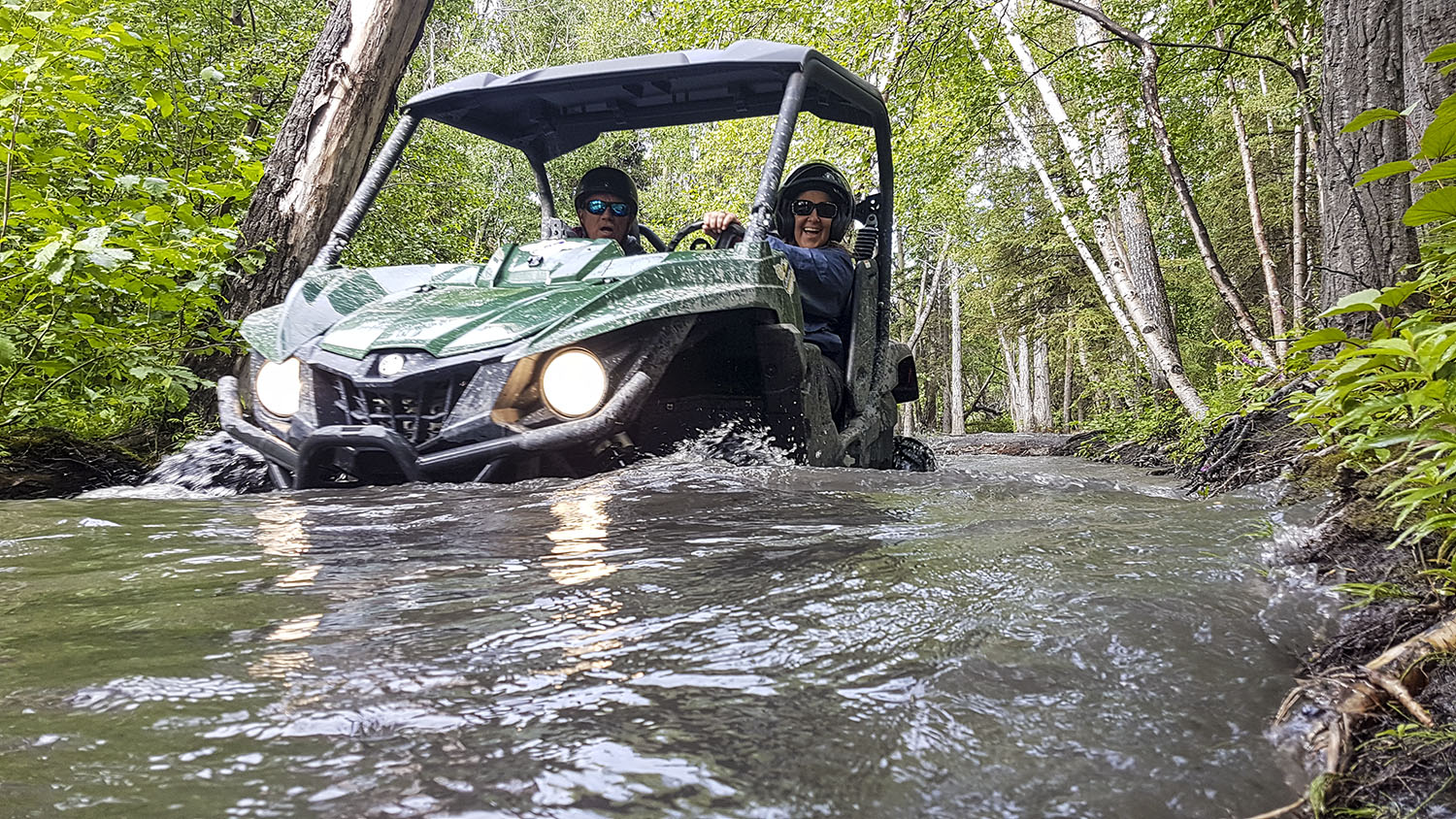 Couple drives UTV through forest pond