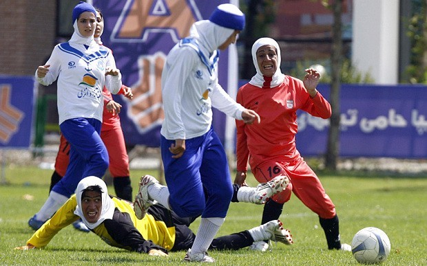 """Iran's """"women"""" national football team (red and yellow) play a friendly football match with club Malavan Anzali football team in Tehran; Source: The Telegraph , Photo: Getty Images"""