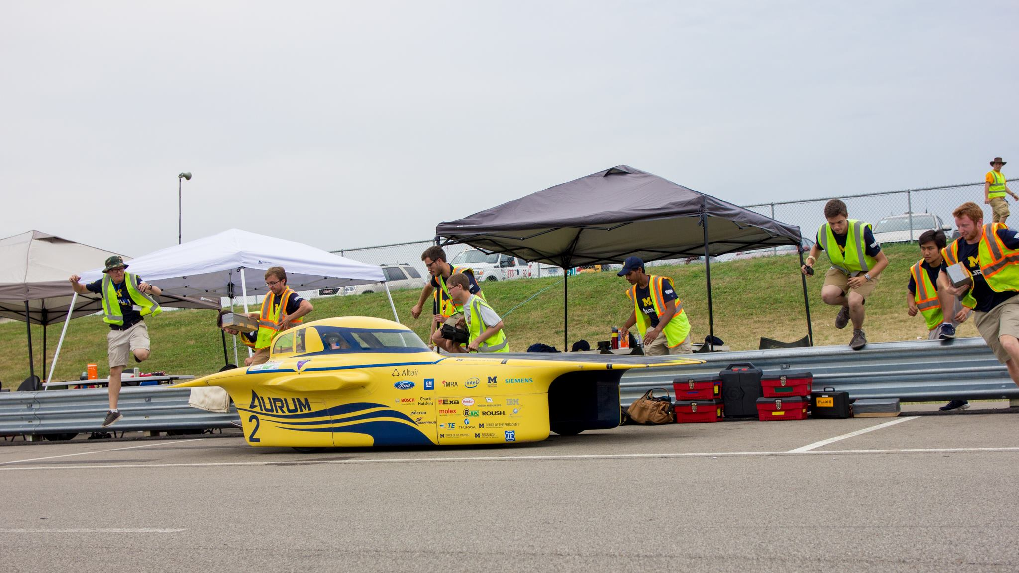 Race crew vaults over the track barrier in preparation for a pit stop.