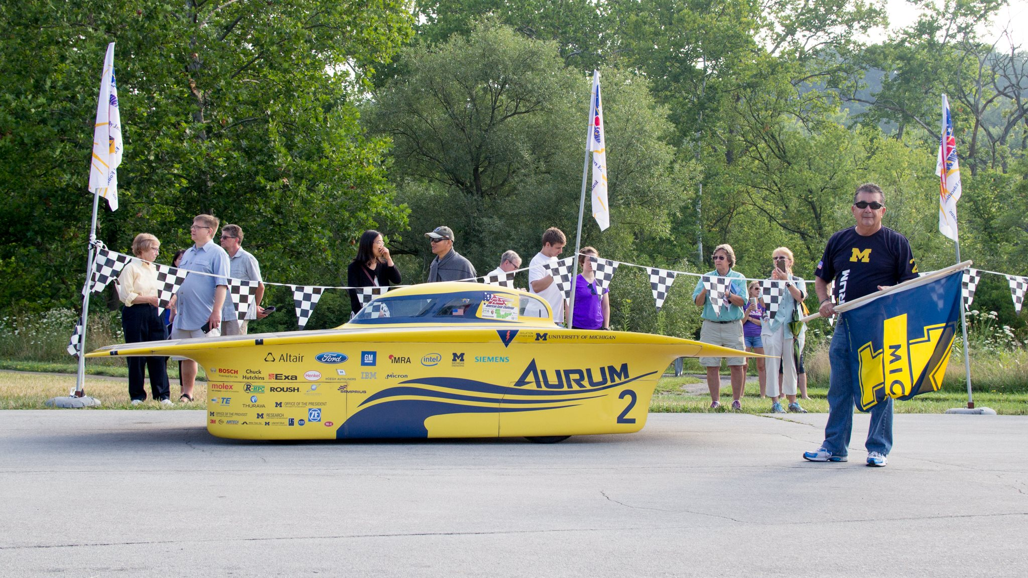 Chito Garcia stands beside Aurum, ready with flag in hand for race start.