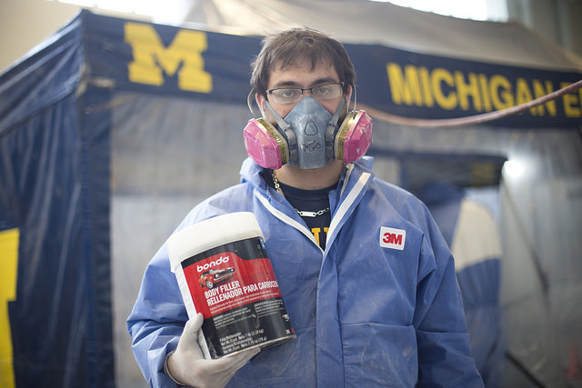 UM Solar Car team member dons 3M protective full-body suit and respirator.