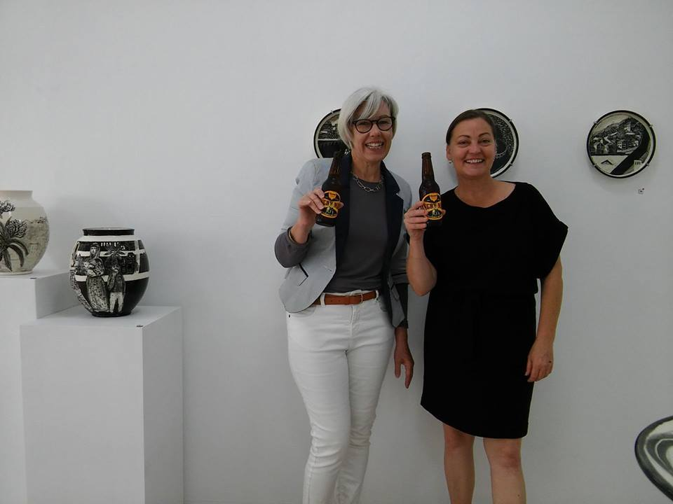 Photo of Gallery 139 volunteers (Catherine and Sharon) during the exhibition of Paul Maher 2018 holding beer sponsored by Murray's Brewing Co