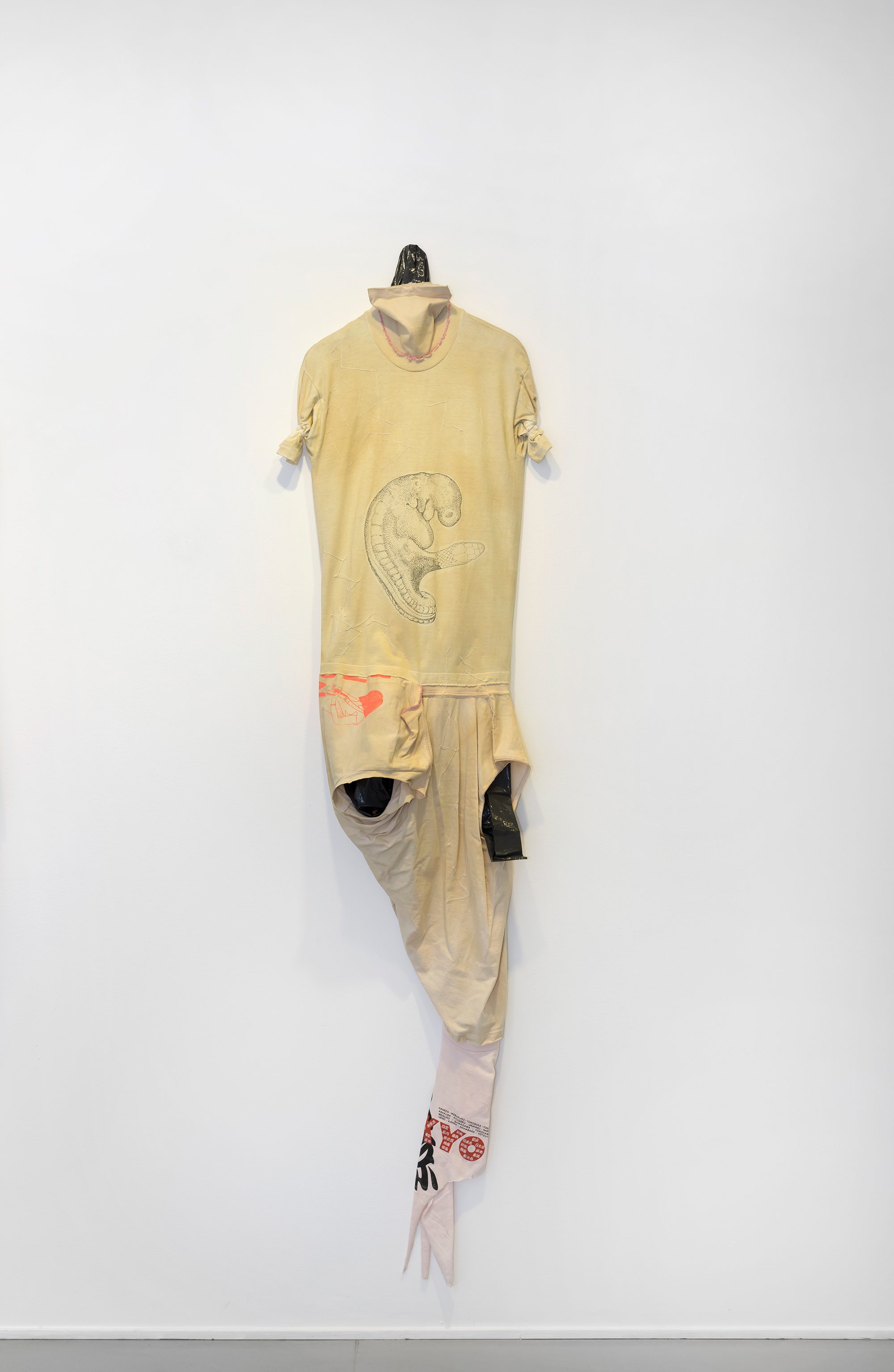 Leif Holmstrand, Costume for a New Tail (It's a Girl) (2015), textile wall sculpture:T-shirt fabric, print depicting human fetus plus snake head,garbage bag plastic, pearls et cetera. Foto: Øystein Thorvaldsen
