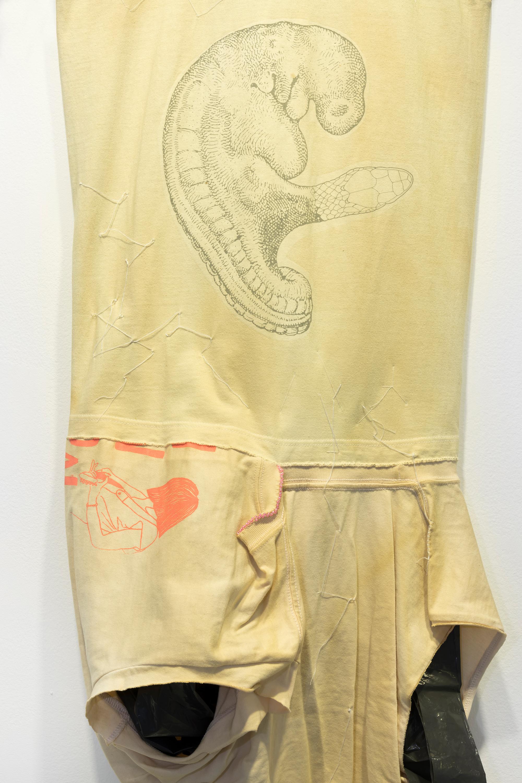 Detalj av Leif Holmstrand, Costume for a New Tail (It's a Girl) (2015), textile wall sculpture:T-shirt fabric, print depicting human fetus plus snake head,garbage bag plastic, pearls et cetera. Foto: Øyvind Thorvaldsen