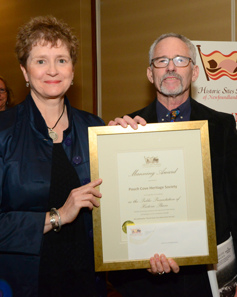 """Ms. Joyce Manning presents the Manning Award to Mr. Dan Rubin of the Pouch Cove Heritage Society, for their publication """"Pouch Cove: Our Home by the Sea""""."""
