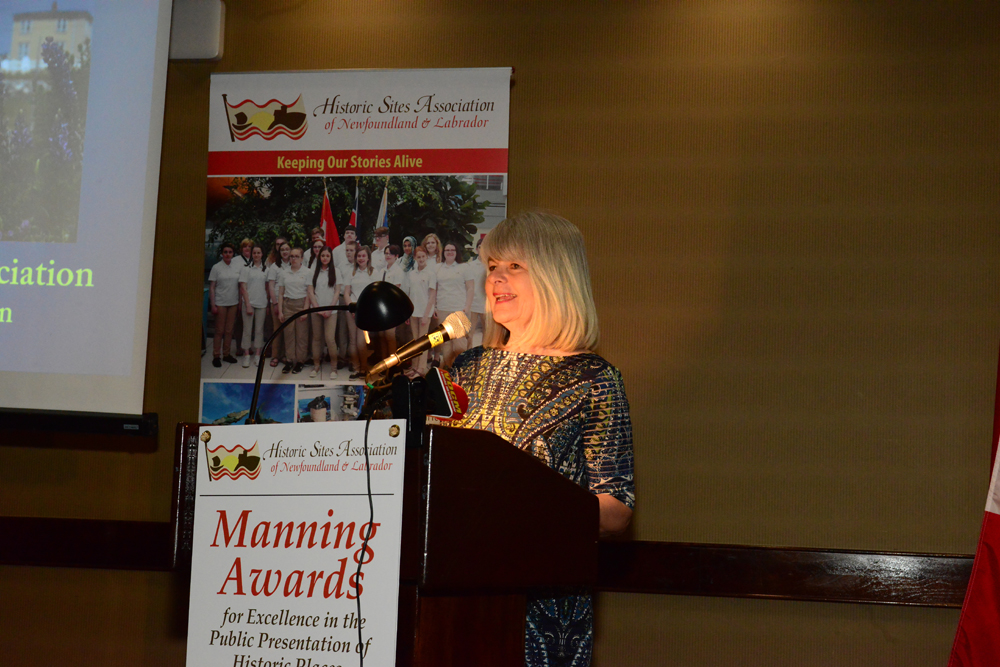 Director Kim Paddon accepting the award on behalf of the English Harbour Arts Association