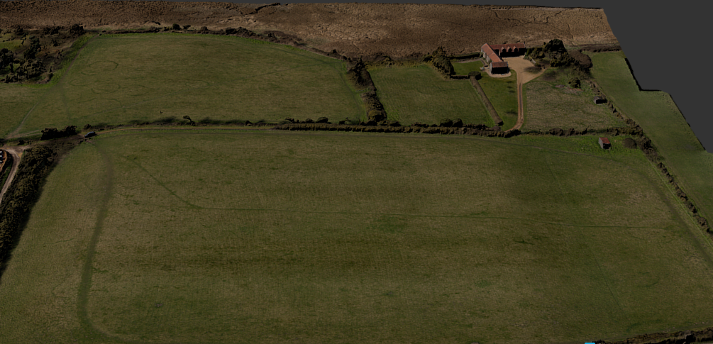 This is a photogrammetric model produced by SUMO Aerial-Cam of Brancaster Roman Fort, showing the raised platform of the fort in the main field and the sea marshes beyond.