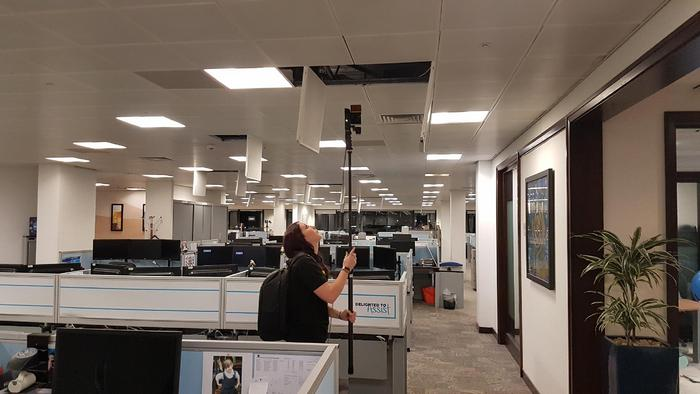 Hand-held laser scanning equipment being used to survey ceiling voids within an office space.