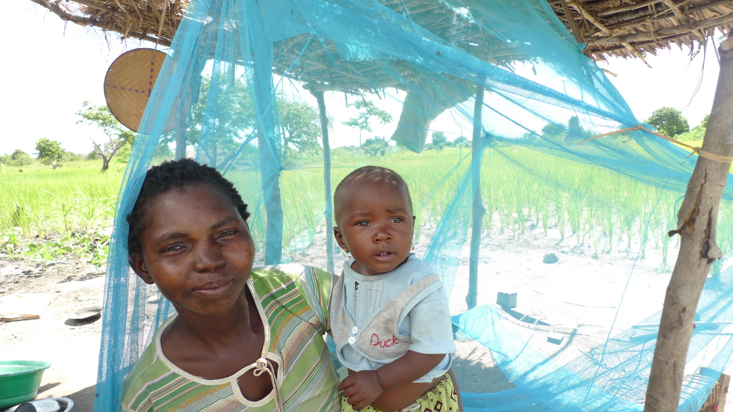 Malaria - mosquito net with Farida.JPG