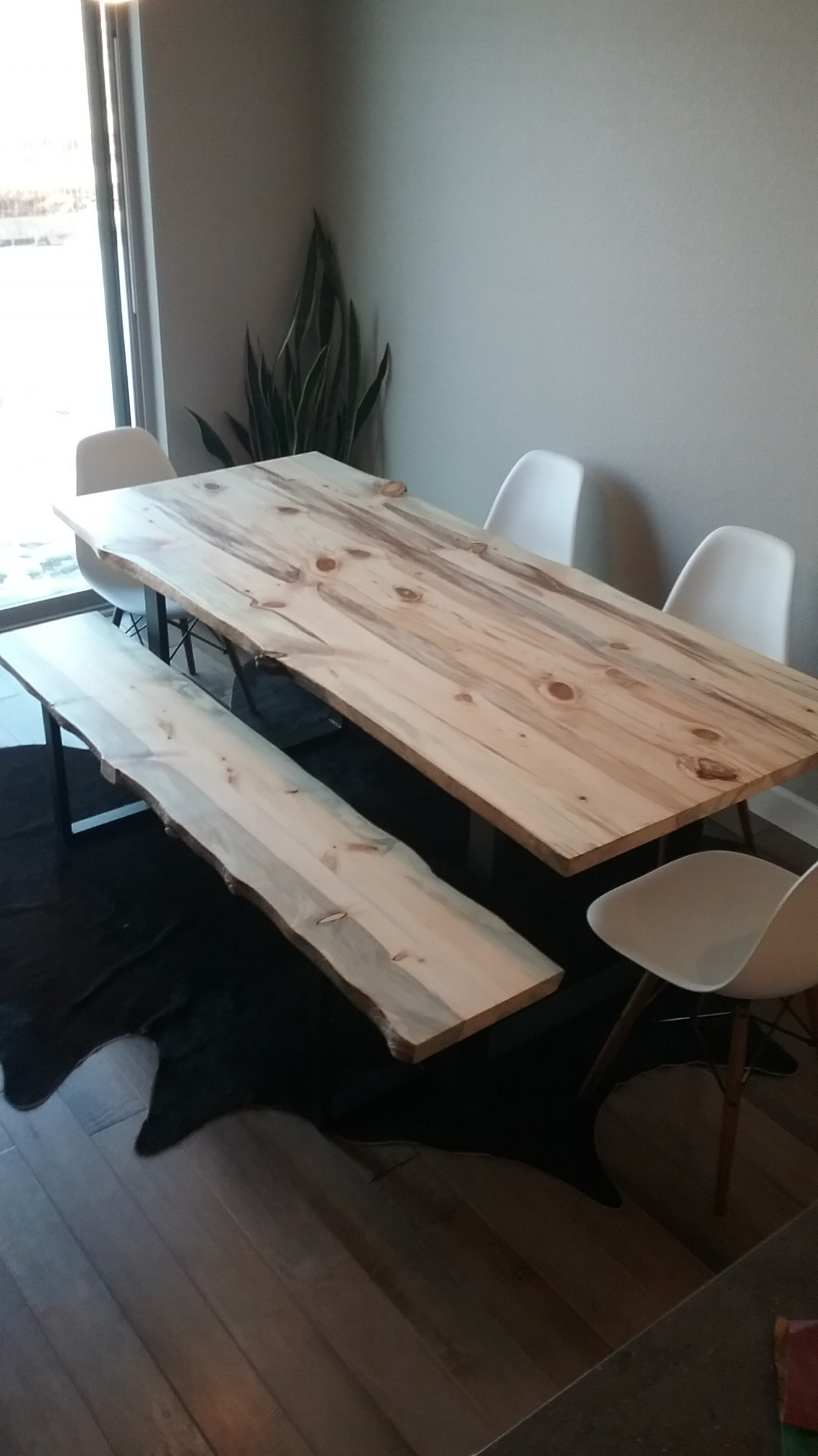 Custom dining table made with three locally harvested beetle slabs. A matching live edge bench, and all resting on a custom fabricated steel frame.