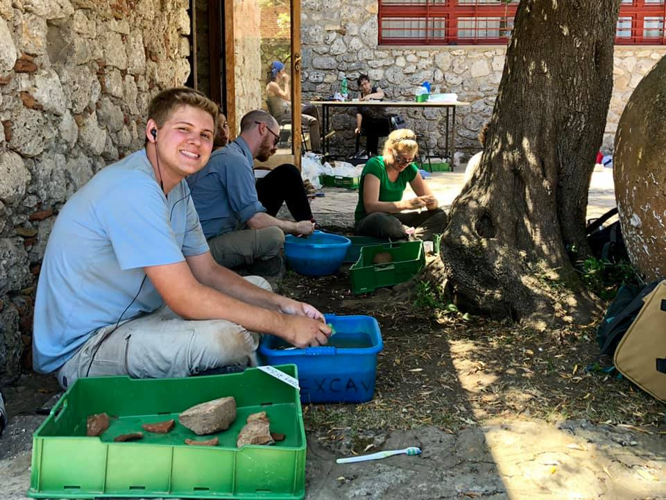 Dawson is all smiles while washing pottery.
