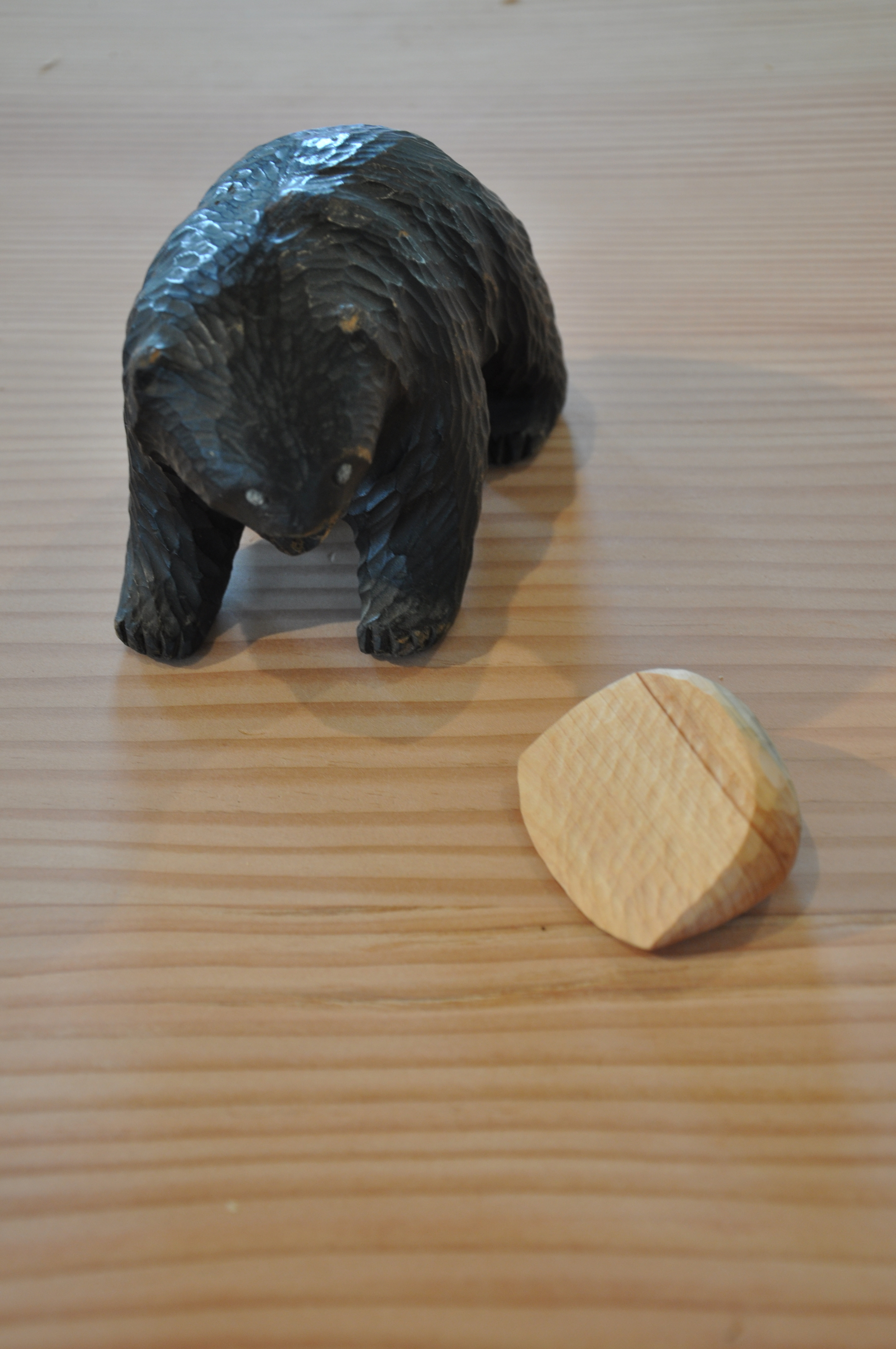 Whittling being evaluated by vintage Ainu bear sculpture