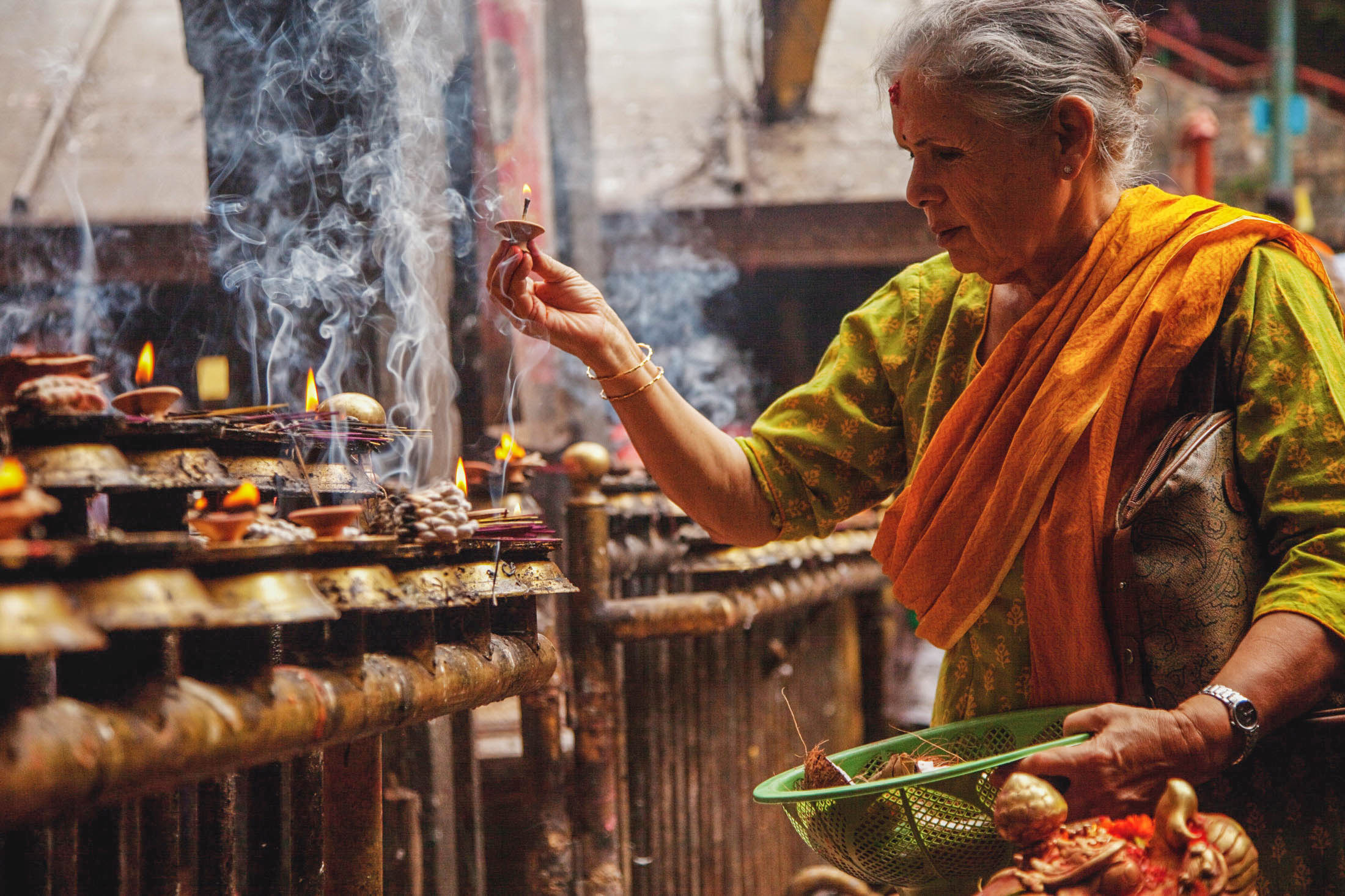 A Hindu worshiper lights candles to gain blessing from Hindu gods at a temple in Nepal. Photo from IMB Photo Library.