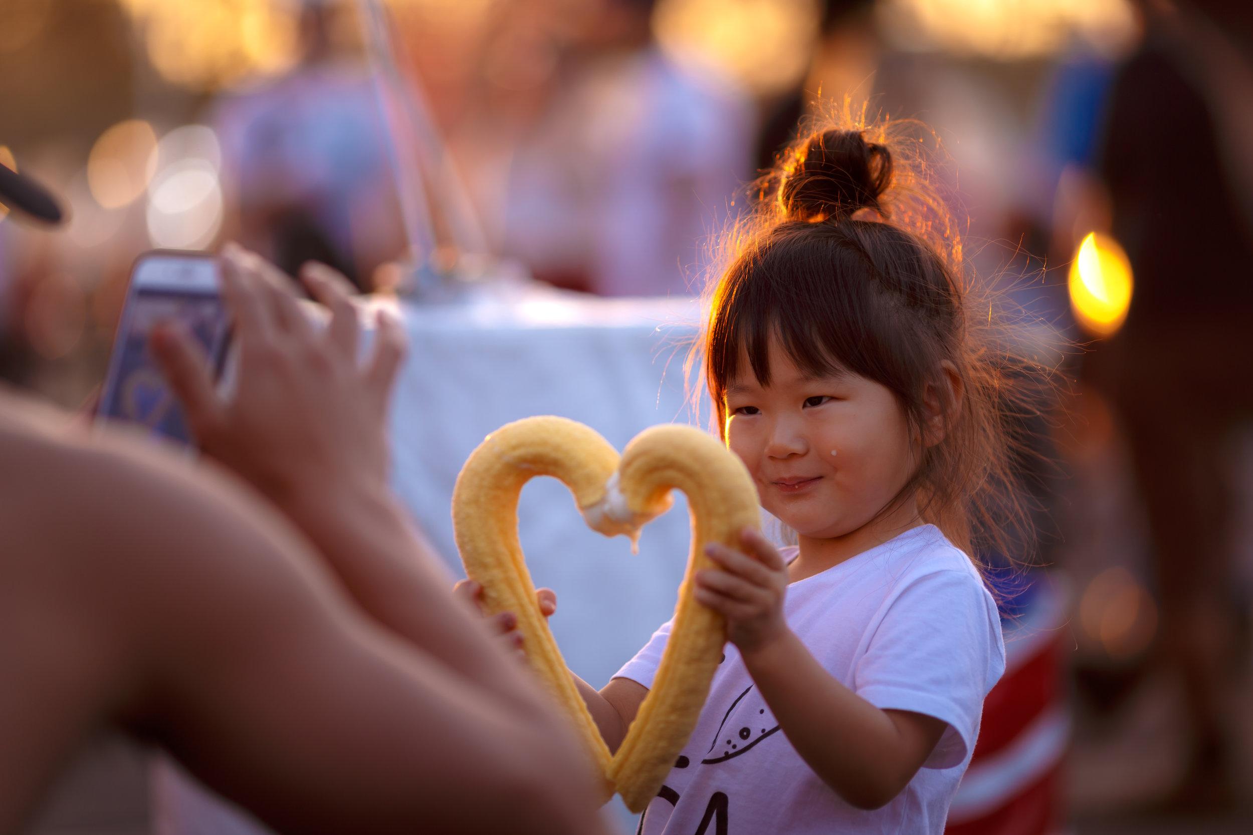 A girl enjoys Hokkaido milk ice cream in J-shaped cones from vendor Hawaiian Honey Cones. Photo by John Truong.