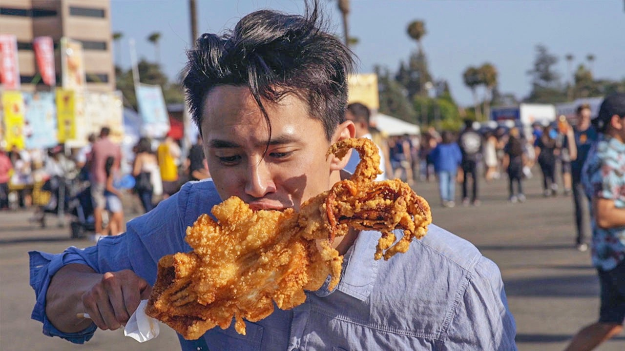 Anthony Ma in Family Style eating giant fried squid at 626 Night Market