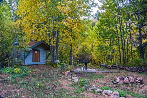 One of our wheelchair accessible huts, surrounded by beautiful aspens and equipped with a grill, water pail and firewood.
