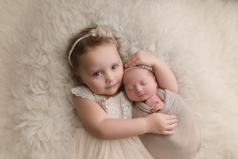 orange-county-newborn-photographer-irvine-studio-siblings-sisters-cute-hugs-toddler-with-newborn.jpg