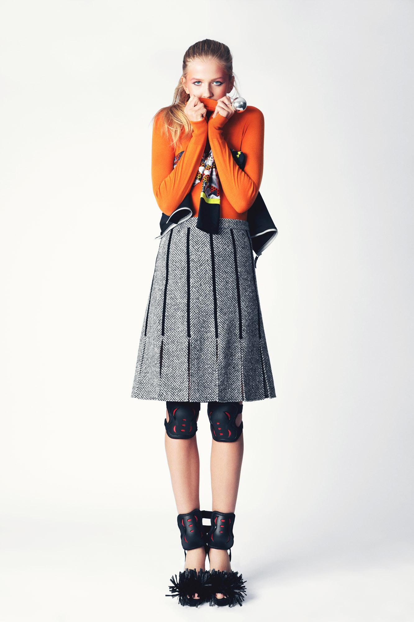 ALDONA wears -Orange Knit Top: KING & TUCKFIELD, Top: SPEEDO, Skirt: CATRIONA HANLEY,Heels: LONGSHAW WARD, Ring: CIVILIAN LONDON,Knee and Elbow pads: SLICK WILLIES