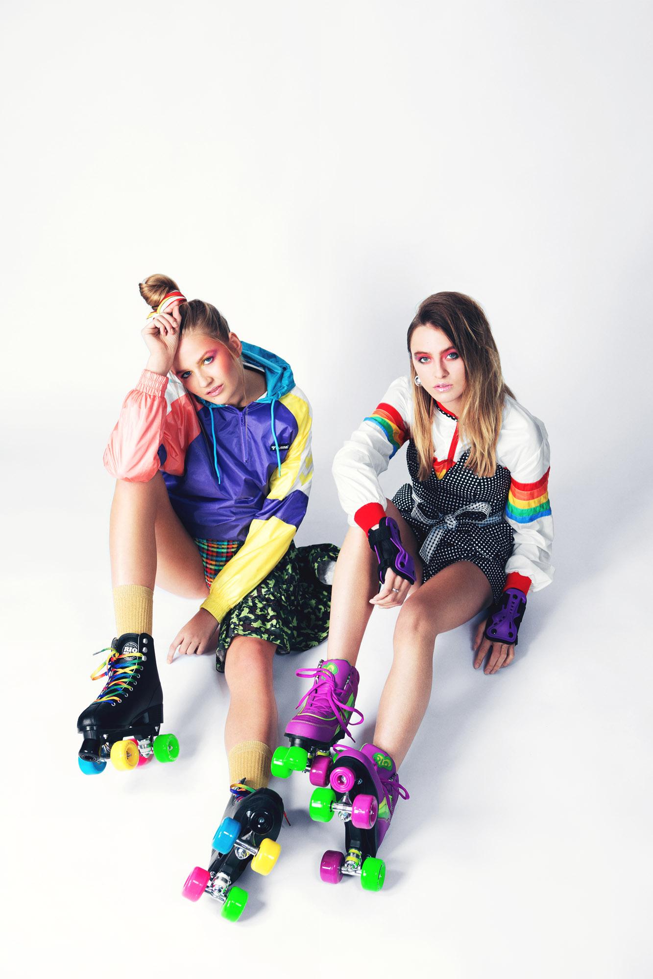 Left  ALDONA wears Tracksuit Jacket: HUMMEL HIVE, Top:LES ANIMAUX,Bikini Set:LILLIPUT & FELIX,Scarf: RIXO LONDON(Young British Designers),Socks:STANCE,Roller Skates: SLICK WILLIES  Right  Phoebe Wright wears Windbreaker: ROKIT, Jumpsuit: C/MEO COLLECTIVE, Earrings: CIVILIAN LONDON,Wrist pads: SLICK WILLIES Roller Skates: SLICK WILLIES