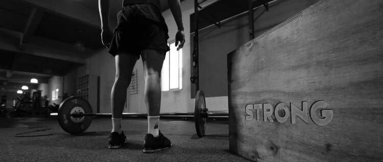 grayscale-photo-of-man-standing-beside-barbell-3112004.jpg