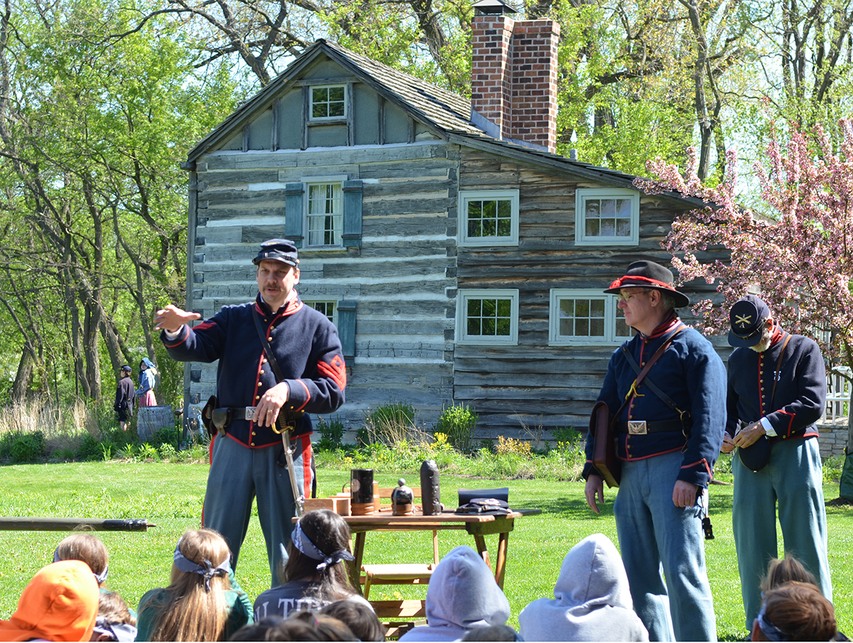 Students listen as a re-enactor discusses battlefield tactics and artillery.