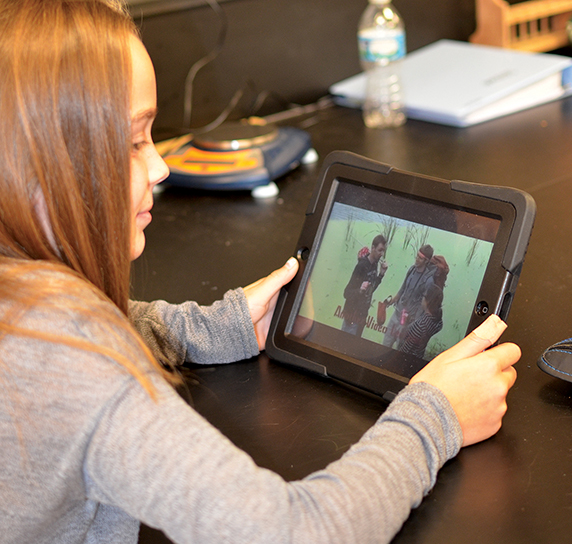 "A student watches a science video in the ""flipped classroom"" model."