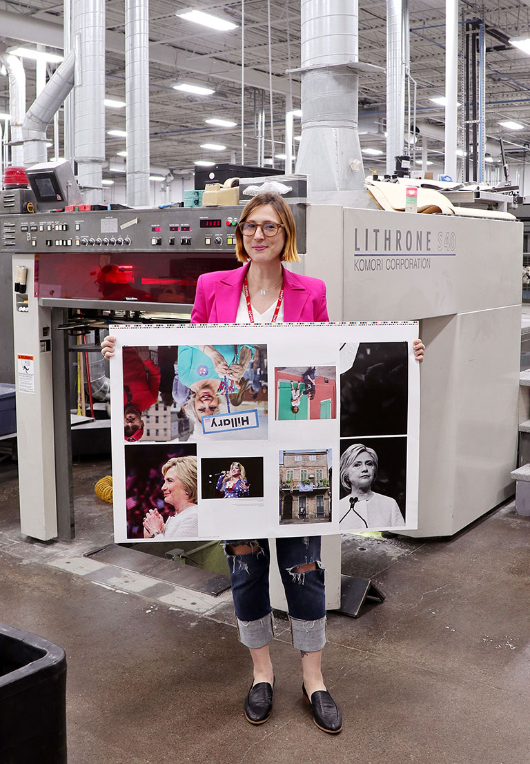Kristen Blush stands in front of the 8-color press at Shapco, Inc, with pages from her book The Revolution Is Female. June 2018.