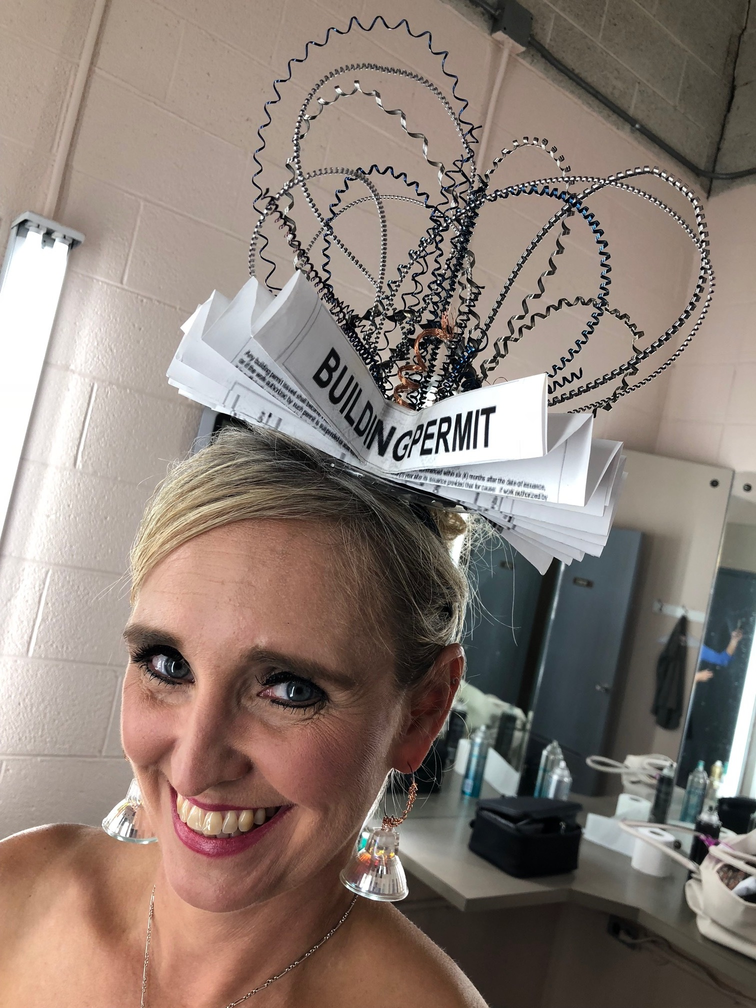 Fascinator made of a building permit, steel and paint samples.