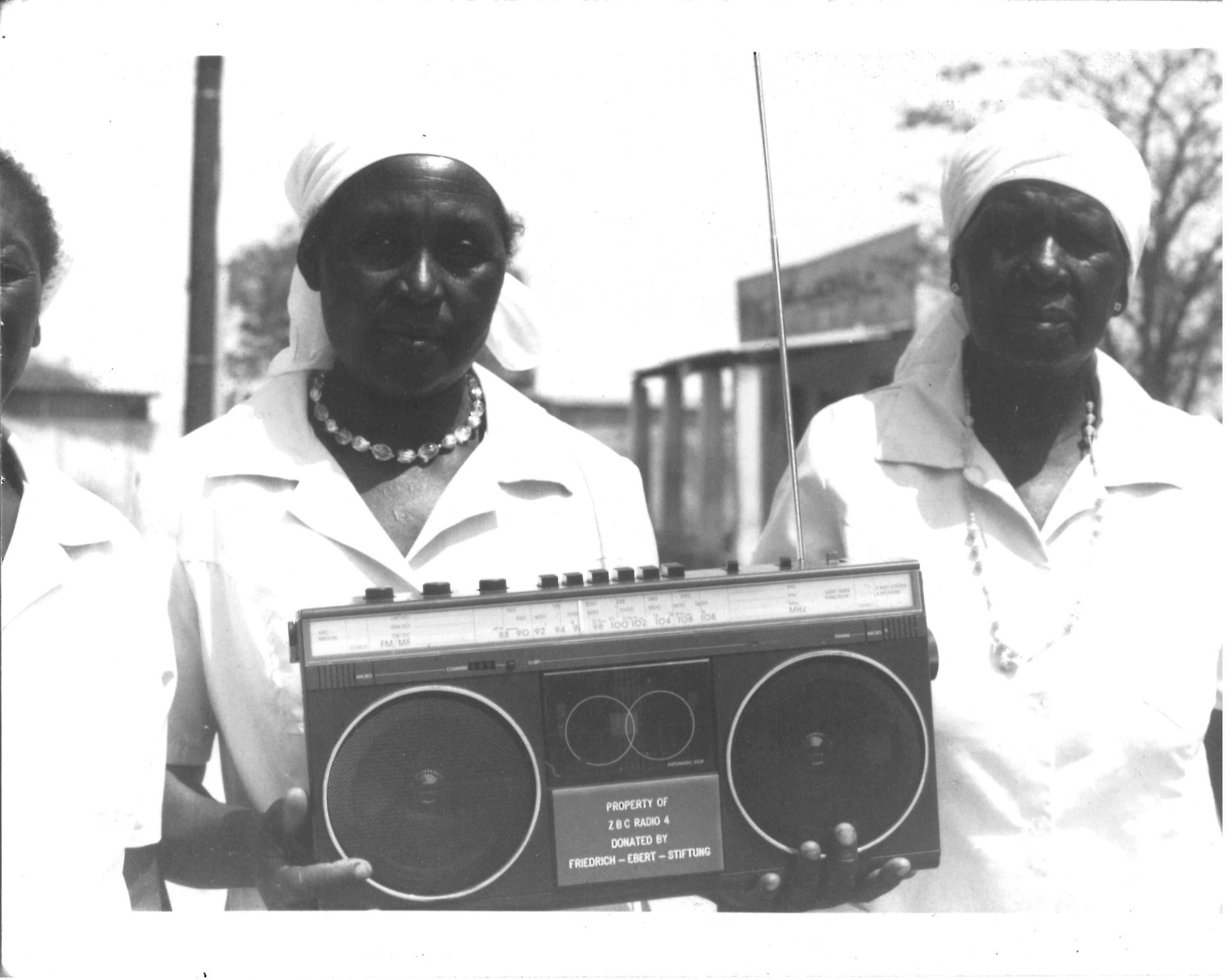 """Image: Two members of the Women's Radio Listening Club in Seke Zimbabwe hold a large radio.""""DTR Clubs - Seke receive free radios from FES [Friedrich Ebert Stiftung] – Germany org.""""];Date 1990s     The owner of the photo is Mavis Mayo and the photographer is Calvin Dondo."""