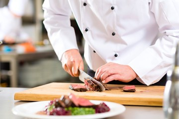 This is an image of a chef cutting meat with a sharp knife on a cutting board.