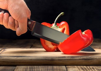 This is an image of a red pepper being sliced with a sharp knife.