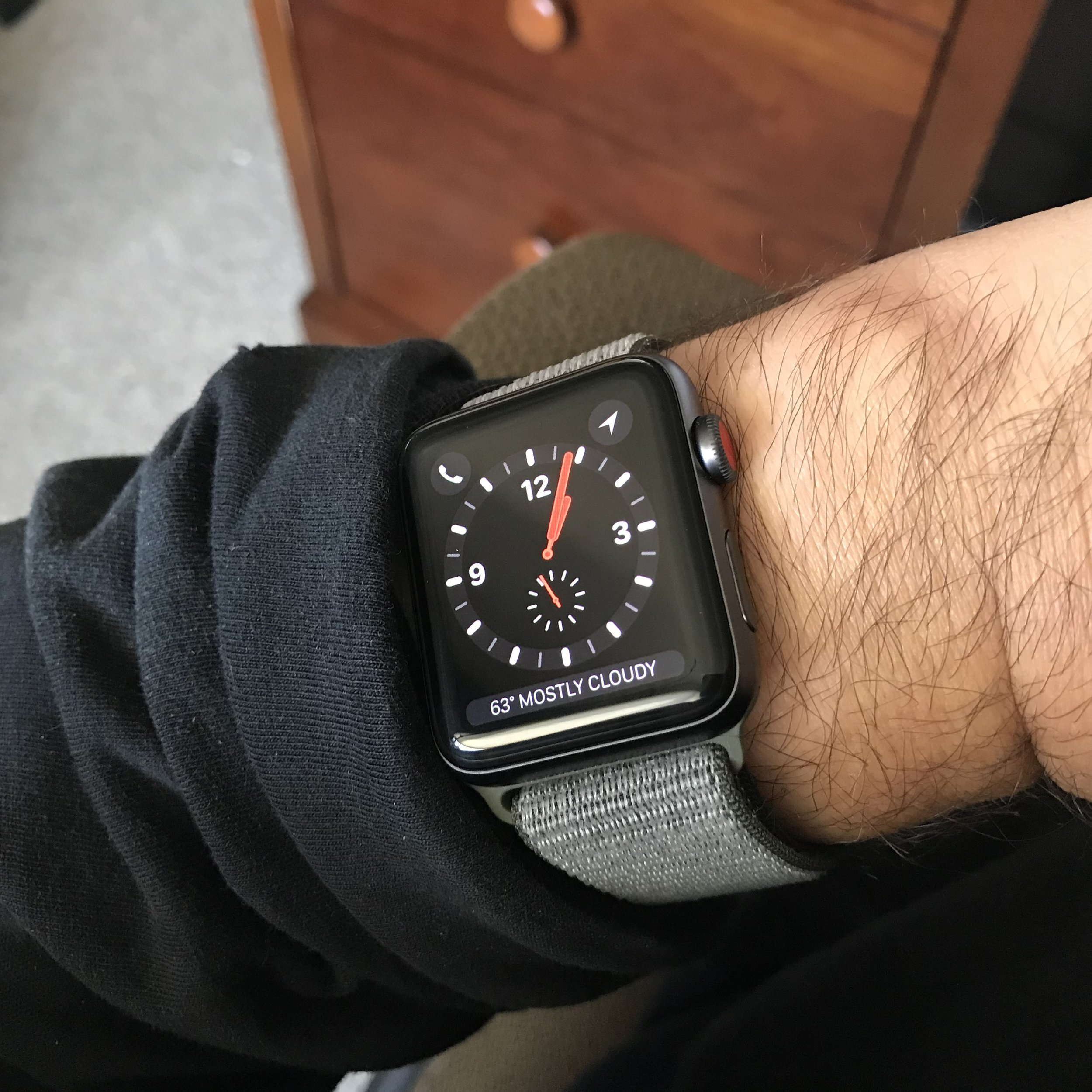 The Apple Watch Series 3 with Cellular, showing the Explorer watch face and the Dark Olive Sport Loop Band