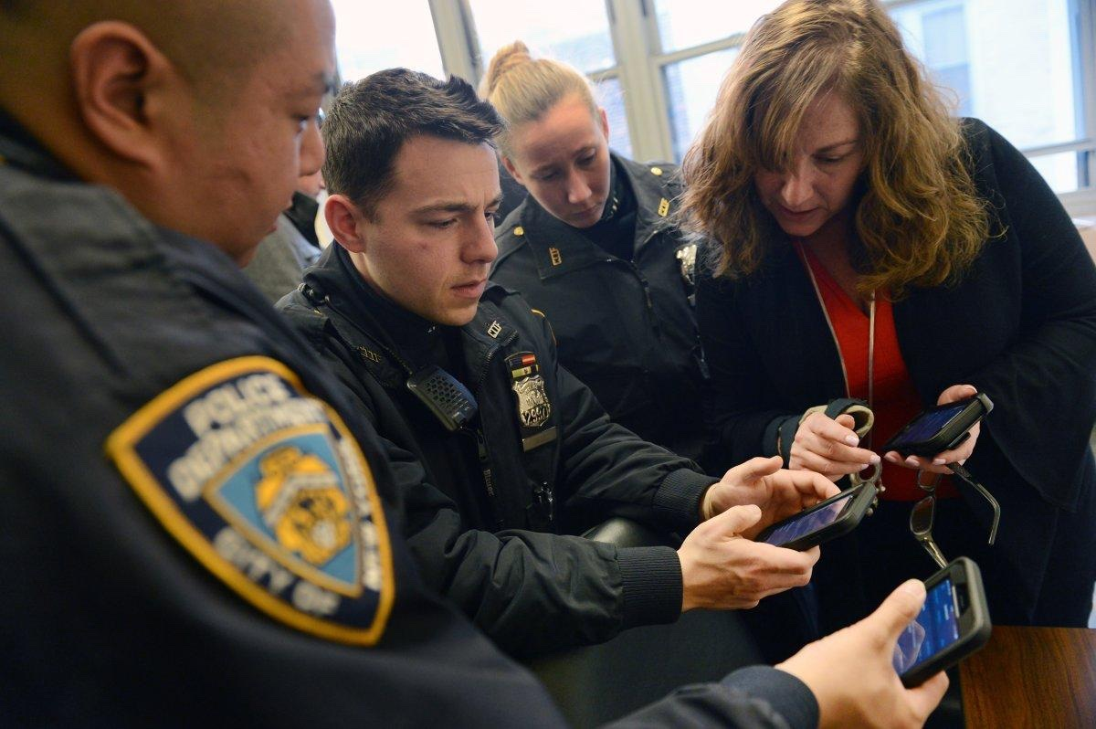 Police officers try out their new iPhones at the 13th Precinct on Thursday, Jan. 25.      (SUSAN WATTS/NEW YORK DAILY NEWS)